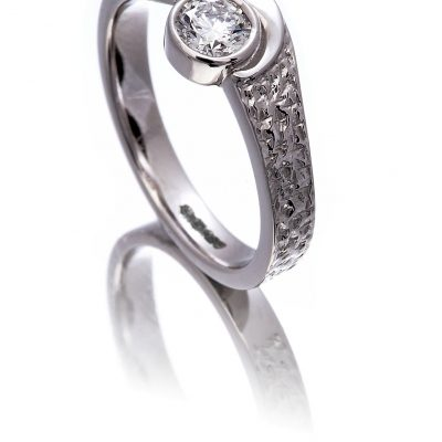 Diamond solitaire ring with a hammered effect finish