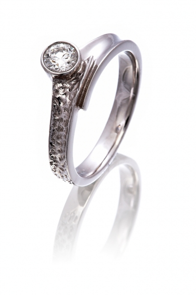 Diamond solitaire cross-over style ring with a hammered effect finish
