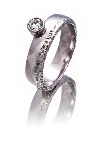 Diamond solitaire ring with a hammered effect edge