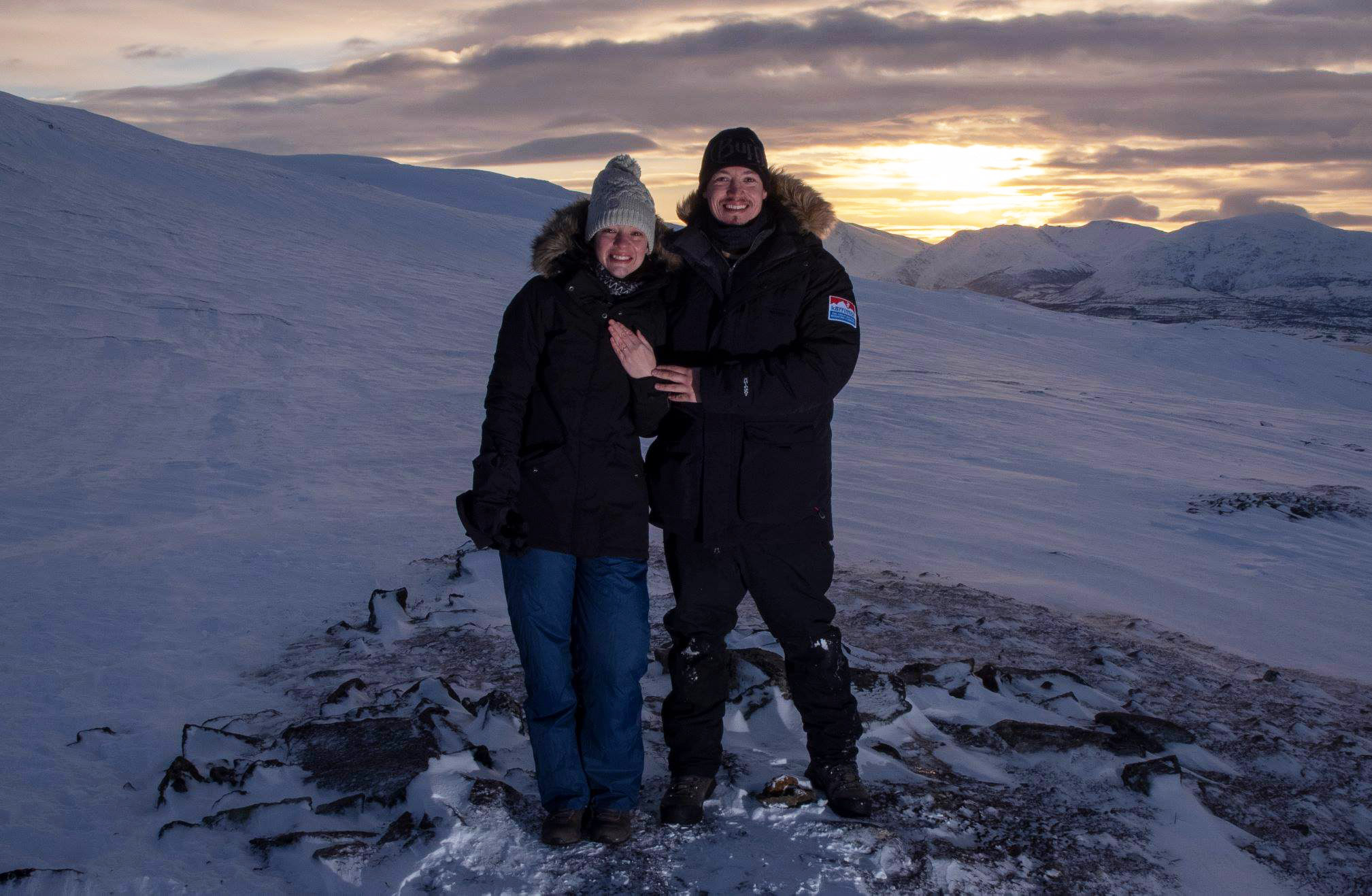 Surprise proposal at sunset in the snow and mountains