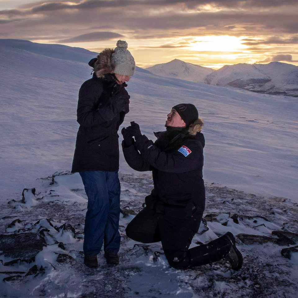 Holiday proposal in Norway on a snow topped mountain at sunset
