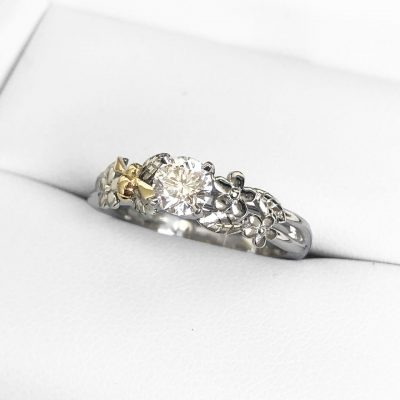 A subtly or slightly asymmetric flower diamond engagement ring