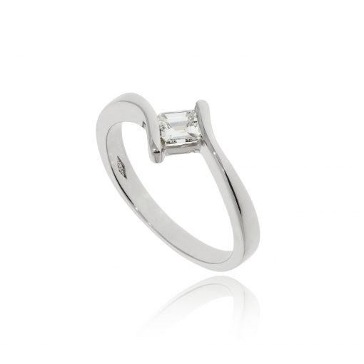 A timeless yet modern white gold crossover emerald cut diamond engagement ring